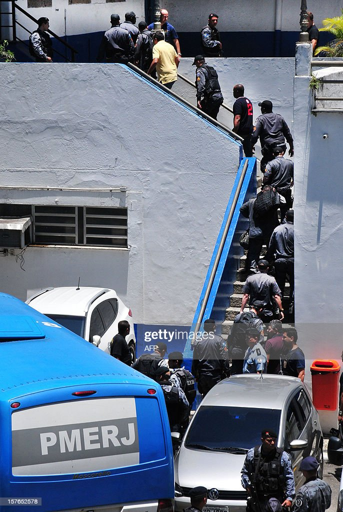 Rio de Janeiro paramilitary police (PM) officers disembark from a bus at the PM headquarters to face charges of receiving bribes from druglords on December 4, 2012 in Rio de Janeiro, Brazil. Sixty-three policemen were arrested in the Purificacion Operation against police corruption launched Monday ensueing a one-year investigation. AFP PHOTO/Estefan Radovicz/Agencia O Dia BRAZIL