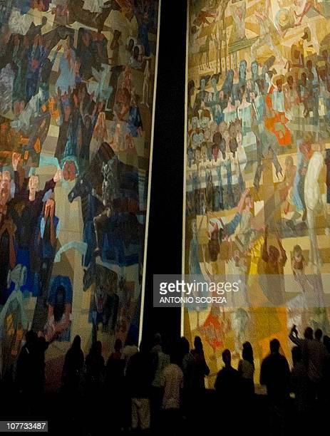 Rio de Janeiro residents and tourists attend a public exhibition of Brazilian painter Candido Portinari's 'War and Peace' painting at the Municipal...