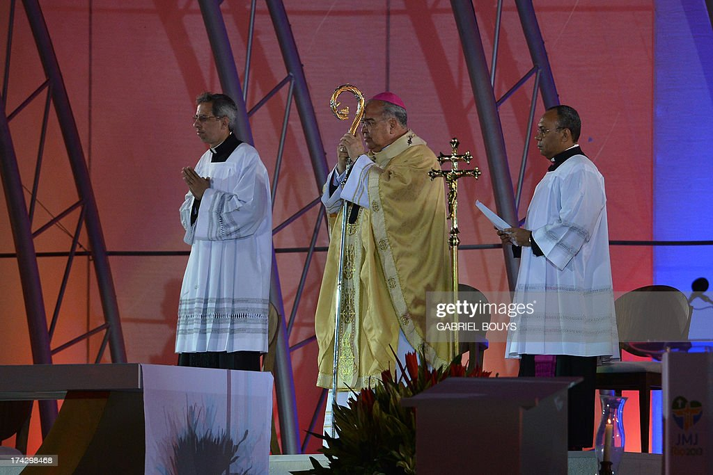 Rio de Janeiro's Archbishop Orani Tempesta (C) officiates during the World Youth Day (WYD) opening mass, at Copacabana beach in Rio de Janeiro, Brazil, on July 23, 2013. The highlight of the landmark visit of Pope Francis to the world's most populous mainly Catholic country will be WYD, a five-day event that kicks off today. Pope Francis's popularity on his Latin American home turf posed a challenge to Brazilian authorities Tuesday after adoring crowds mobbed his car on his arrival on Monday. AFP PHOTO / GABRIEL BOUYS