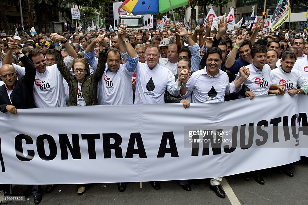 Rio de Janeiro's mayor Eduardo Paes (2nd L) and Rio's governor Sergio Cabral (4th L) walk during a demonstration demanding Brazilian President Dilma Roussef to veto a bill that would redistribute oil royalties in favor of non-oil producing states, in Rio de Janeiro, Brazil, on November 26, 2012. Both Paes and Cabral warned that the new oil royalties share-out plan will jeopardize the financing of the 2014 World Cup and the 2016 summer Olympics. AFP PHOTO/Christophe Simon