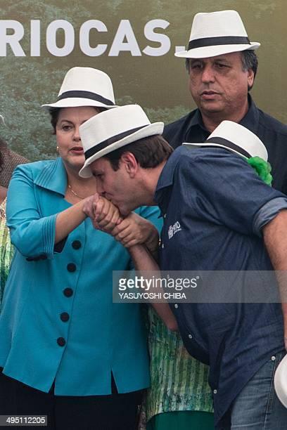 Rio de Janeiro's Mayor Eduardo Paes kisses Brazilian President Dilma Rousseff's hand in front of Rio de Janeiro's Governor Luiz Fernando de Souza...