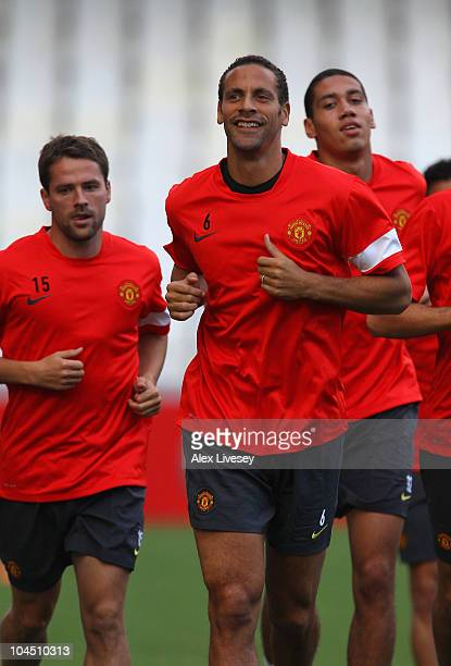 Rio Ferdinand and Michael Owen of Manchester United warm up during a training session ahead of their UEFA Champions League Group C match against...