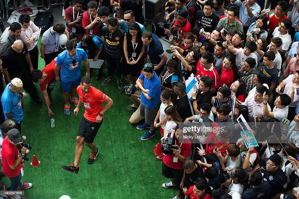 Rio Ferdinand and Sergio Aguero of Manchester City play games with supporters during a meet-the-fans session on May 16, 2014 in Singapore.