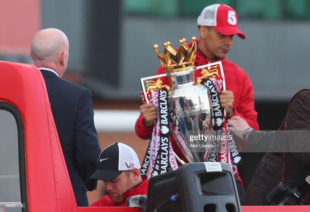 Rio Ferdinand holds the Barclays Premier League trophy onboard the open topped bus outside Old Trafford as Wayne Rooney (C,L) looks down during the Manchester United Premier League winners parade on May 13, 2013 in Manchester, England.