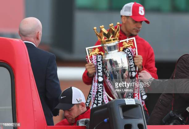 Rio Ferdinand holds the Barclays Premier League trophy onboard the open topped bus outside Old Trafford as Wayne Rooney looks down during the...