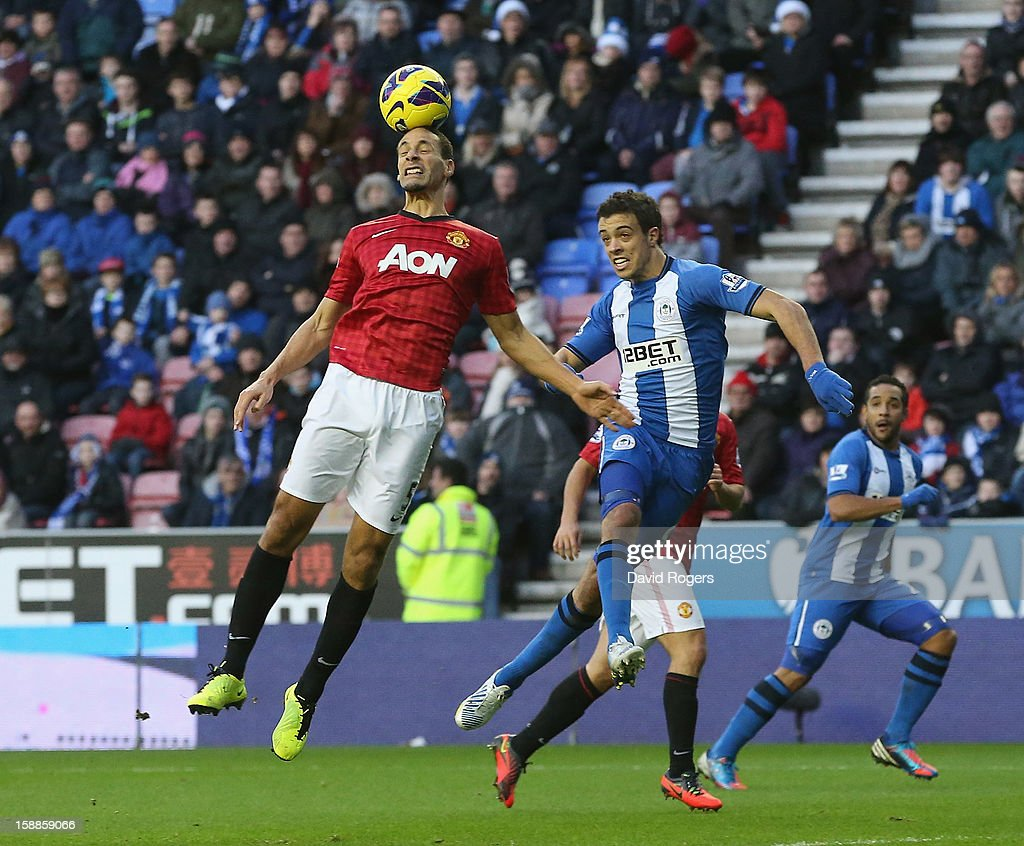 Rio Ferdinand of Manchester United heads the ball as Franco di Santo challenges during the Barclays Premier League match between Wigan Athletic and Manchester United at the DW Stadium on January 1, 2013 in Wigan, England.