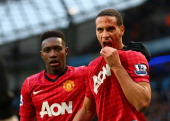 Rio Ferdinand of Manchester United is helped by teammate Danny Welbeck after being struck by an object during the Barclays Premier League match...