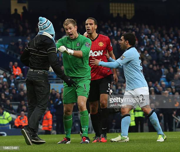 Rio Ferdinand of Manchester United Joe Hart and Carlos Tevez of Manchester City apprehend a pitch invader during the Barclays Premier League match...