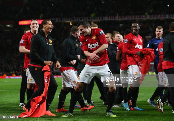 Rio Ferdinand of Manchester United tries to pull Robin van Persie's shorts as they celebrate winning the Premier League title after the Barclays...