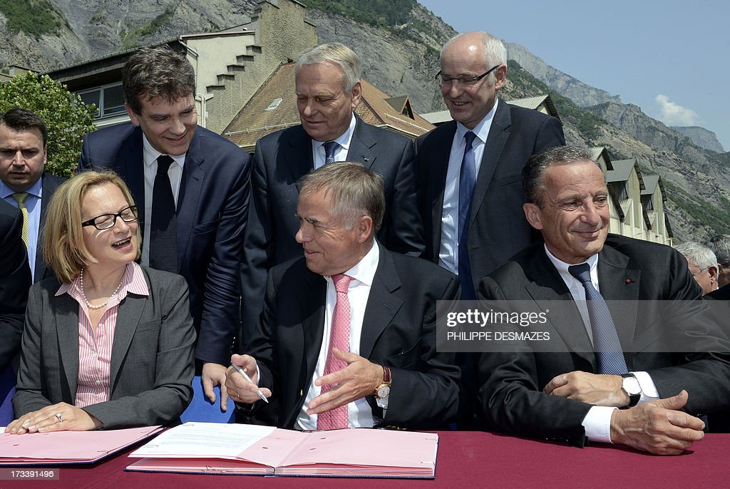 Rio Tinto Alcan chief executive officer Jacynte Côte and the president of TRIMET, German Heinz-Peter Schlüter, sign on July 13, 2013 a contract next to Chairman and CEO of EDF Henri Proglio under the supervision of (back LtoR) French Minister for Industrial Renewal and Food Industry Arnaud Montebourg, French Prime minister Jean-Marc Ayrault, and French Junior Minister for European Affairs Thierry Repentin at the Rio Tinto Alcan (RTA) aluminum factory in Saint-Jean-de-Maurienne, southeast of France. Heads of Rio Tinto Alcan and Germany's Trimet met today in Paris regarding the take over of RTA by Trimet which could save 510 jobs at the two sites of Saint-Jean-de-Maurienne and Castelsarrasin.
