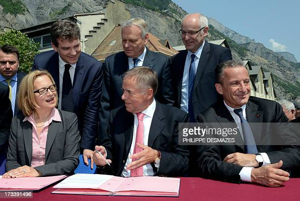 Rio Tinto Alcan chief executive officer Jacynte Côte and the president of TRIMET German HeinzPeter Schlüter sign on July 13 2013 a contract next to...