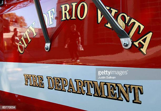 Rio Vista firefighters are seen reflected in the door of a rescue vehicle as they check equipment November 20 2008 in Rio Vista California The...