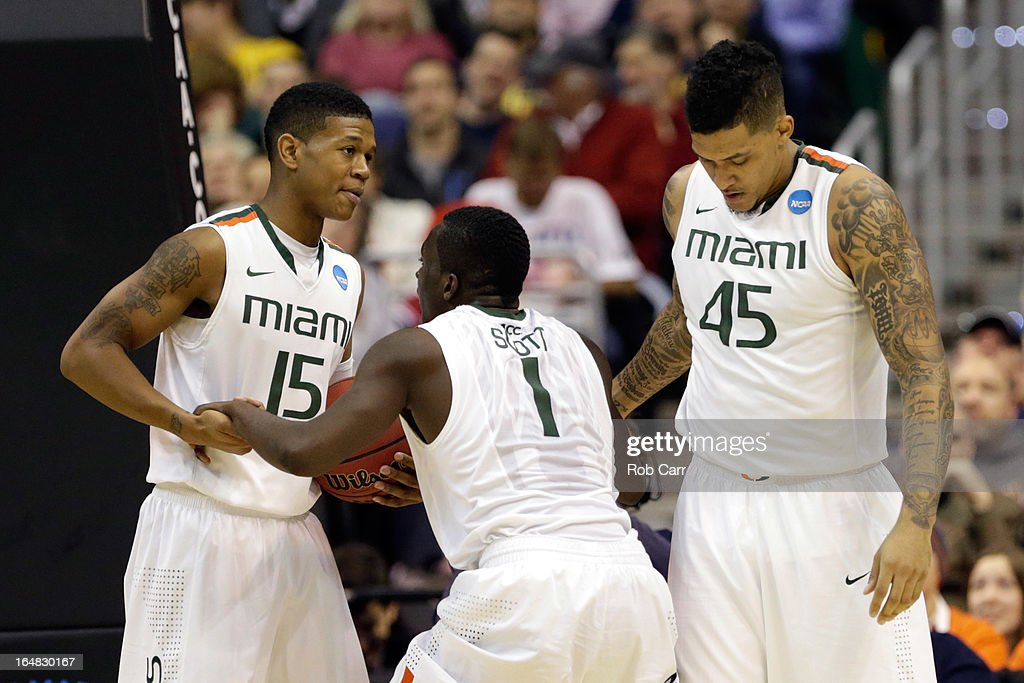 Rion Brown #15 and Julian Gamble #45 of the Miami (Fl) Hurricanes help up teammates Durand Scott #1 against the Marquette Golden Eagles during the East Regional Round of the 2013 NCAA Men's Basketball Tournament at Verizon Center on March 28, 2013 in Washington, DC.
