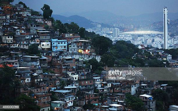 Rio's iconic Maracana Stadium is lit at dusk behind a shanytown or 'favela' on December 10 2013 in Rio de Janeiro Brazil The stadium will host the...