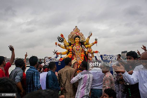 Riot of colours choked emotions mingle as Hindus give fond farewell to Durga for a year Durga Puja the worshipping of the Mother Goddess and her...
