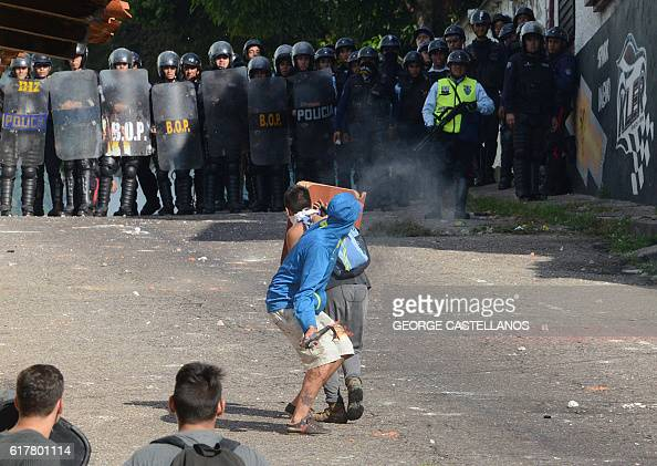 TOPSHOT Riot police agents confront students opponent to Nicolas Maduro's government in San Cristobal state of Tachira Venezuela on October 24 2016...