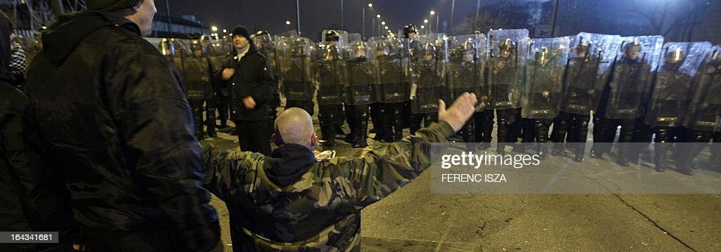 Riot police and Hungarian fans confront each other outside of the Puskas stadium after the Hungary vs Romania FIFA 2014 World Cup qualifying football match in Budapest, on March 22, 2013. FIFA ordered Hungary to play the 2014 World Cup qualifier match behind closed doors after fans hurled anti-Semitic abuse during a friendly match with Israel in August 2012.