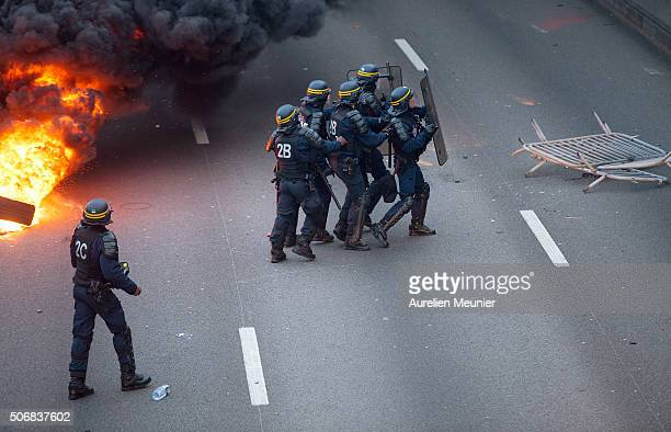 Riot police are protecting themselves as taxis demonstrate by blocking the traffic on the peripherique by setting tires on fire on January 26 2016 in...