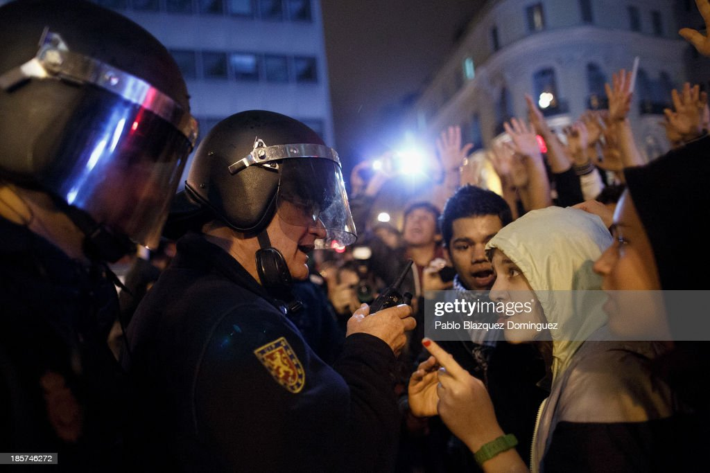 Riot police argue with protesters after a demonstration at Alcala Street on October 24, 2013 in Madrid, Spain. The Spanish Parliament recently approved a controversial reform of the educational system, which passed by the ruling right wing People's Party (PP) using their absolute majority and not backed by any other political party. The students are on a three day strike to protest against the new law, which will need to be approved by the senate next month and are calling for the resignation of Education Minister, Jose Ignacio Wert.
