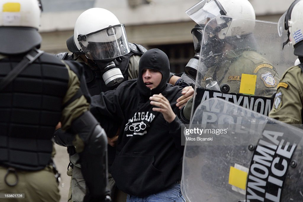 Riot police arrest a demonstrator during a protest against German Chancellor Angela Merkel's visit to Greece on October 9, 2012 in Athens, Greece. Merkel arrived in Greece on her first visit since Europe's debt crisis erupted here three years ago, braving protests to deliver a message of support to a nation hammered by recession and fighting to stay in the euro.