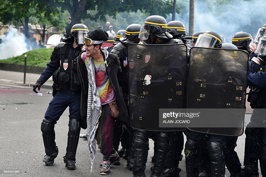 Riot police arrest a demonstrator during a protest against the government's labour market reforms in Paris, on May 26, 2016. The French government's labour market proposals, which are designed to make it easier for companies to hire and fire, have sparked a series of nationwide protests and strikes over the past three months. / AFP / ALAIN