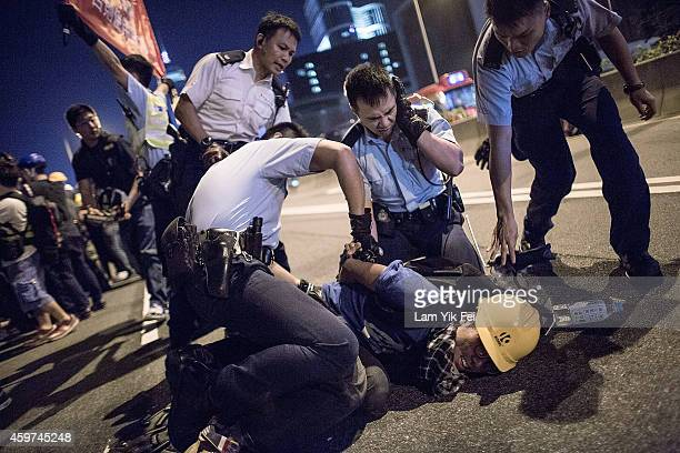 Riot police arrest a prodemocracy protester during clash outside Central Government Complex on November 30 2014 in Hong Kong According to reports...