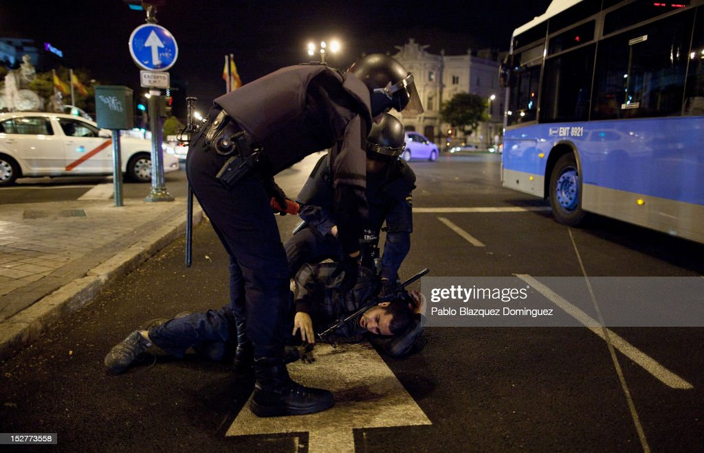 Riot police arrest a protester at Cibeles during a demonstrations surrounding the Spanish Parliament on September 25, 2012 in Madrid, Spain. Demonstrators from various organizations, demanding a new constitutional process, are marching today from three different locations in the center of Madrid to the lower house in the Spanish parliament.