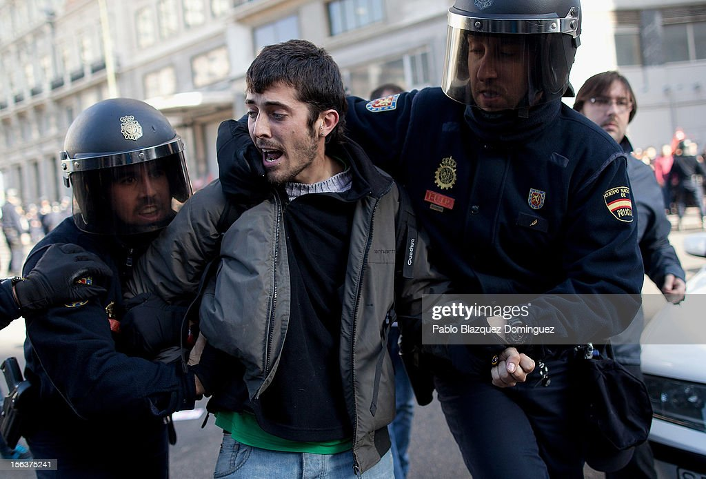 Riot police arrest a protester during a demonstration at Gran Via on November 14, 2012 in Madrid, Spain. A coordinated general strike by unions in Spain and Portugal has paralysed public transport in the two countries with further strikes planned across Europe. The strike against the governments' austerity measures have force hundreds of flights to be cancelled and factories and ports to come to a standstill.