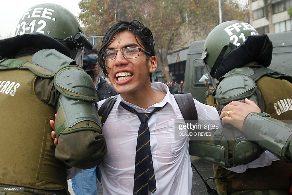 Riot police arrest a student during a march held to protest the slow pace of educational reform, in Santiago, on May 26, 2016. / AFP / CLAUDIO