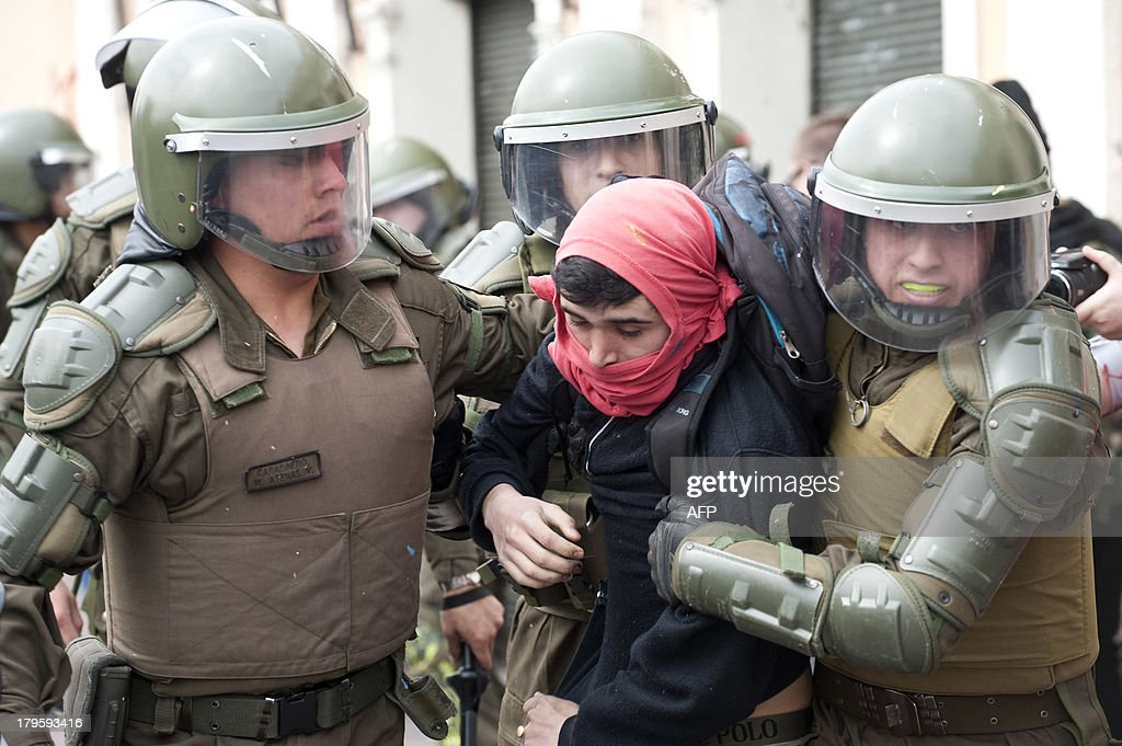 Riot police arrest a student during a protest to demand Chilean President Sebastian Pinera's government an intensive educational reform and to break with other legacies of the dictatorship of Augusto Pinochet (1973-1990), in Santiago, on September 5, 2013. AFP PHOTO/Claudio SANTANA