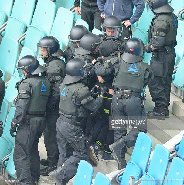 Riot police arrest a supporter during the Regionalliga Playoff First Leg match between between Rasenballsport Leipzig and Sportfreunde Lotte at Red...