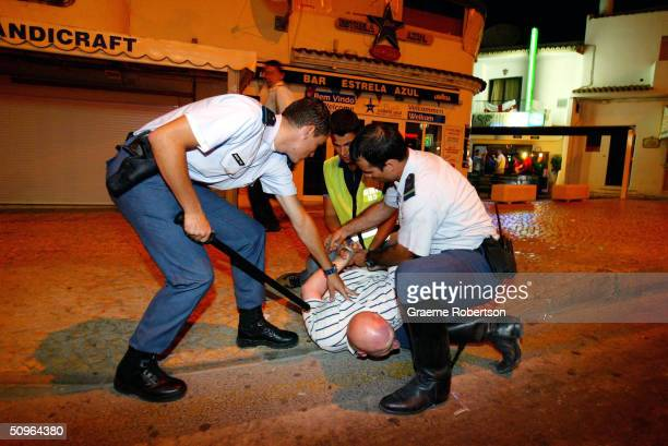 Riot police arrest England fans after they start trouble June 15 2004 in Albufeira a city in the Algarve region of Portugal Large groups of England...