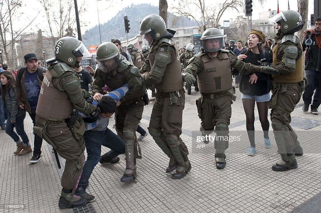 Riot police arrest students during a protest to demand Chilean President Sebastian Pinera's government an intensive educational reform and to break with other legacies of the dictatorship of Augusto Pinochet (1973-1990), in Santiago, on September 5, 2013. AFP PHOTO/Claudio SANTANA