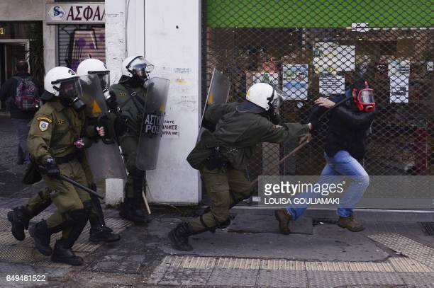 TOPSHOT Riot police attempt to detain a man during a protest by Greek farmers against higher taxes outside the Agriculture ministry in Athens on...