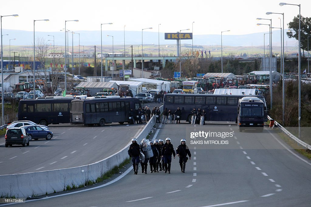 Riot police block on February 11, 2013 the highway to farmers, seeking to blockade the highway between Thessaloniki and Athens in Nikaia, some 380 kms north of Athens. Protesting Greek farmers, who are demanding tax breaks and other benefits, have refused an offer from the Greek government after a February 10 meeting and they said they would not relent and keep their tractors positioned at key points on major roads across Greece, which they have continually threatened to blockade unless they get everything they want. AFP PHOTO /SAKIS MITROLIDIS