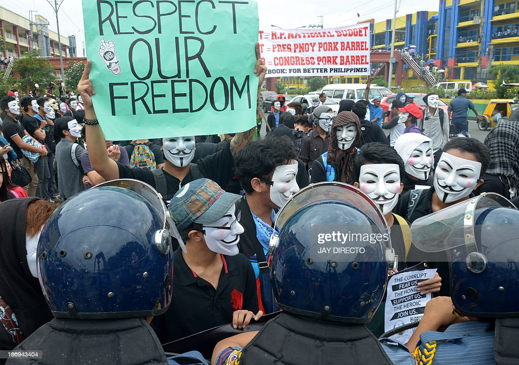 Riot police block protesters wearing Guy Fawkes masks during a rally outside the House of Representatives in suburban Quezon city, north of Manila on November 5, 2013. Some 100 masked members of the hacking group Anonymous Philippines marched on parliament on November 5, denouncing corruption and pledging more cyber attacks, a week after 30 government websites were paralysed. AFP PHOTO / Jay DIRECTO