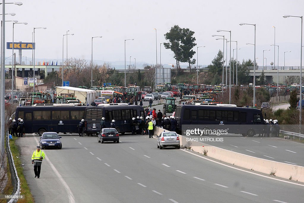 Riot police block with police buses the road in Nikaia, some 380kms north of Athens and 1km before the National Highway Thessaloniki-Athens, on January 29, 2013.Protesting farmers moved their tractors near the national highway on Tuesday morning threatening to block the traffic on Greece's North-South axis. However the farmers were hindered from parking their tractors on the highway by strong riot police forces.Farmers claim that this year's production is at risk of collapsing due to lack of liquidity and dramatic increase in taxation. AFP PHOTO /Sakis Mitrolidis