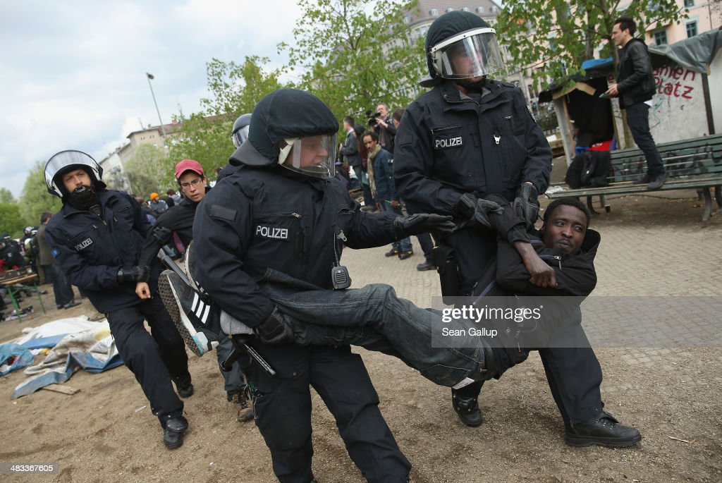 Riot police carry away a young protester after they intervened at the former temporary refugee camp at Oranienplatz in Kreuzberg district on April 8, 2014 in Berlin, Germany. Several hundred riot police sealed off the square after, according to an eyewitness, violence broke out between refugees who had accepted a deal by the city to leave the camp and a small number who insisted on staying. Refugees, many of them from Africa who came to Germany via Lampedusa, began dismantling their shelters today after many of them agreed to a deal with city authorities to move to a renovated hostel. Not all of the several hundred refugees, some of whom have been living at the Oranienplatz camp almost a year, have agreed to the deal, and while some said they will go elsewhere, some insisted they will stay, despite a city order to vacate.