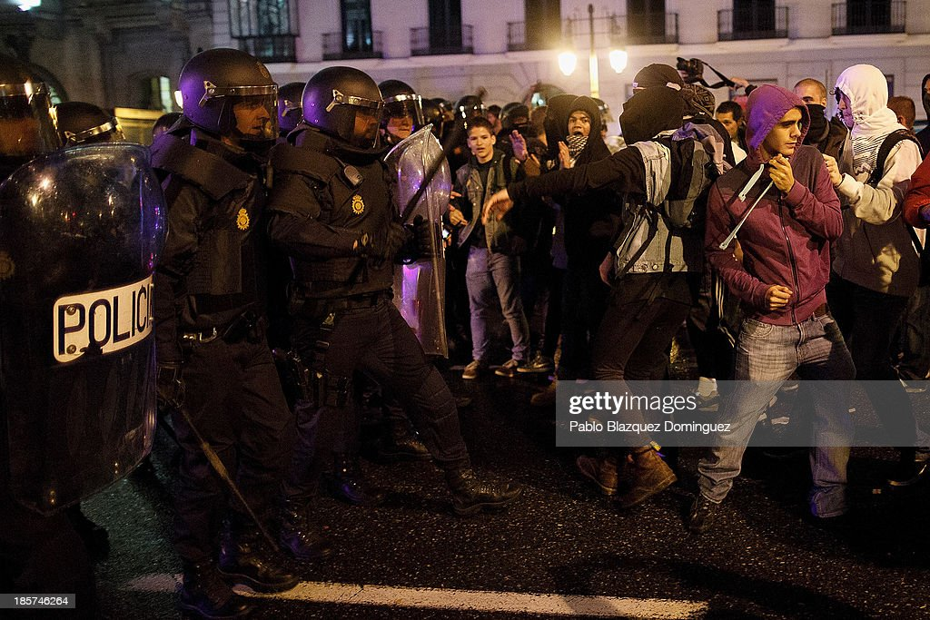 Riot police chase protesters after a demonstration at Alcala Street on October 24, 2013 in Madrid, Spain. The Spanish Parliament recently approved a controversial reform of the educational system, which passed by the ruling right wing People's Party (PP) using their absolute majority and not backed by any other political party. The students are on a three day strike to protest against the new law, which will need to be approved by the senate next month and are calling for the resignation of Education Minister, Jose Ignacio Wert.