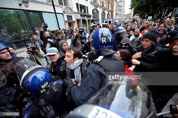 Riot police clash with activists near a building thought to be an anticapitalist squat in central London on June 11 as few hunderd protesters took to...