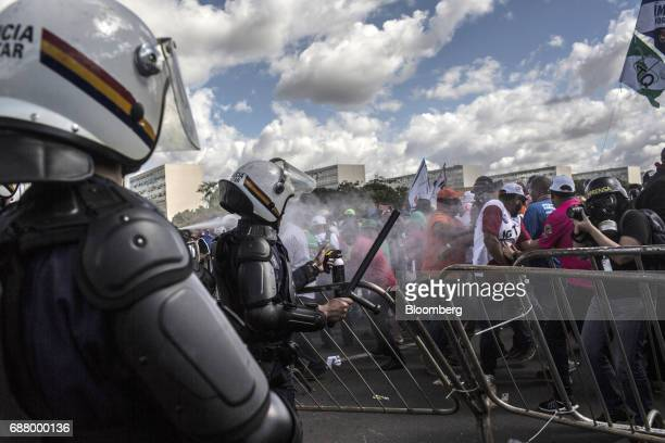 Riot police clash with demonstrators during protests outside of the National Congress demanding the resignation of President Michel Temer in Brasilia...