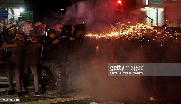 TOPSHOT Riot police clash with supporters of Dilma Rousseff as they protest against new Brazilian President Michel Temer at the Paulista Avenue in...