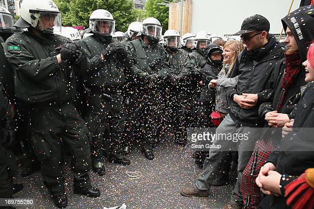 Riot police confronting demonstrators are inundated with colored confetti during the main Blockupy demonstration in the financial district on June 1...