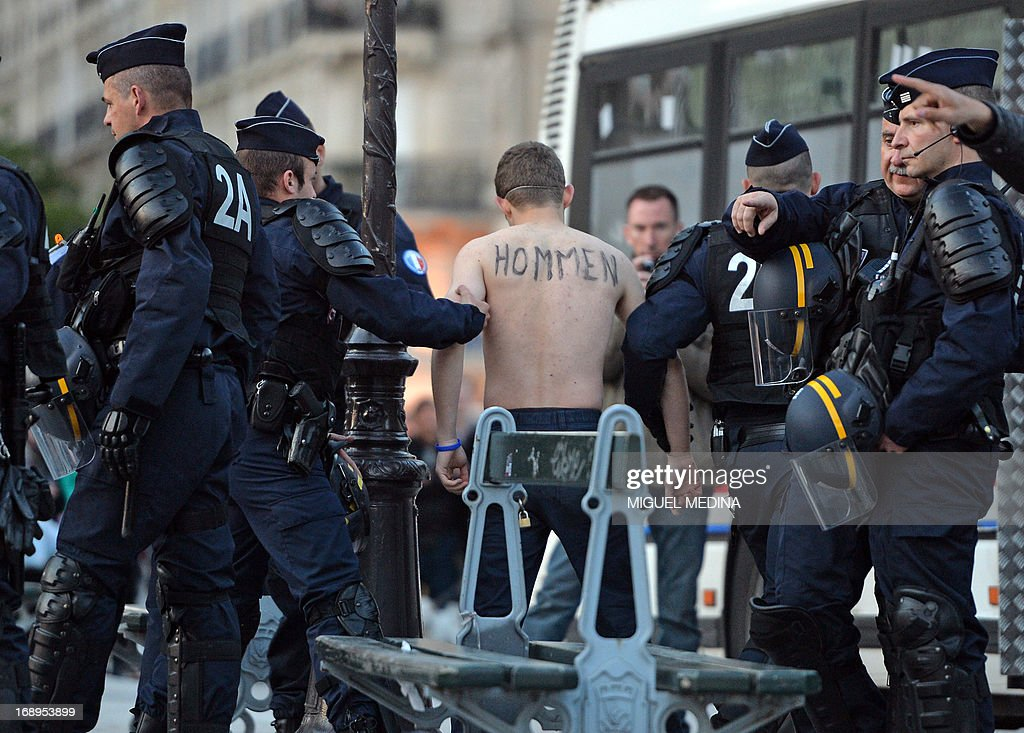 Riot police detain a bare-chested man belonging to an anti-gay group (Hommen) during a demonstration against a bill legalizing same sex marriages on May 17, 2013 in Paris. After months of acrimonious debate and hundreds of protests that have occasionally spilled over into violence, France's National Assembly approved on April 23, 2013 a bill making the country the 14th to legalise same-sex marriage. AFP PHOTO / MIGUEL MEDINA