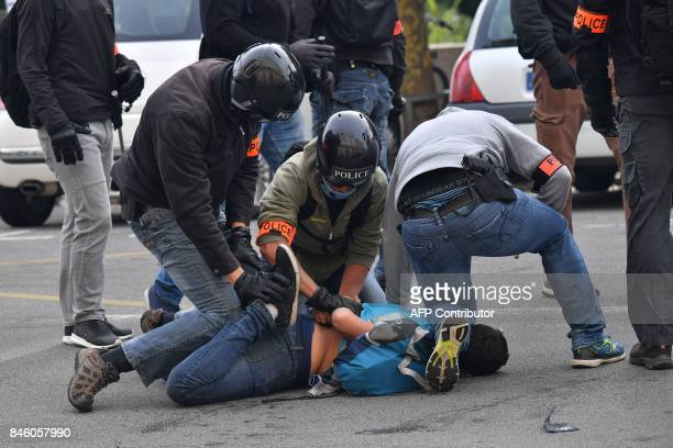 Riot police detain a demonstrator in Nantes western France on September 12 2017 during a protest called by several French unions against the labour...