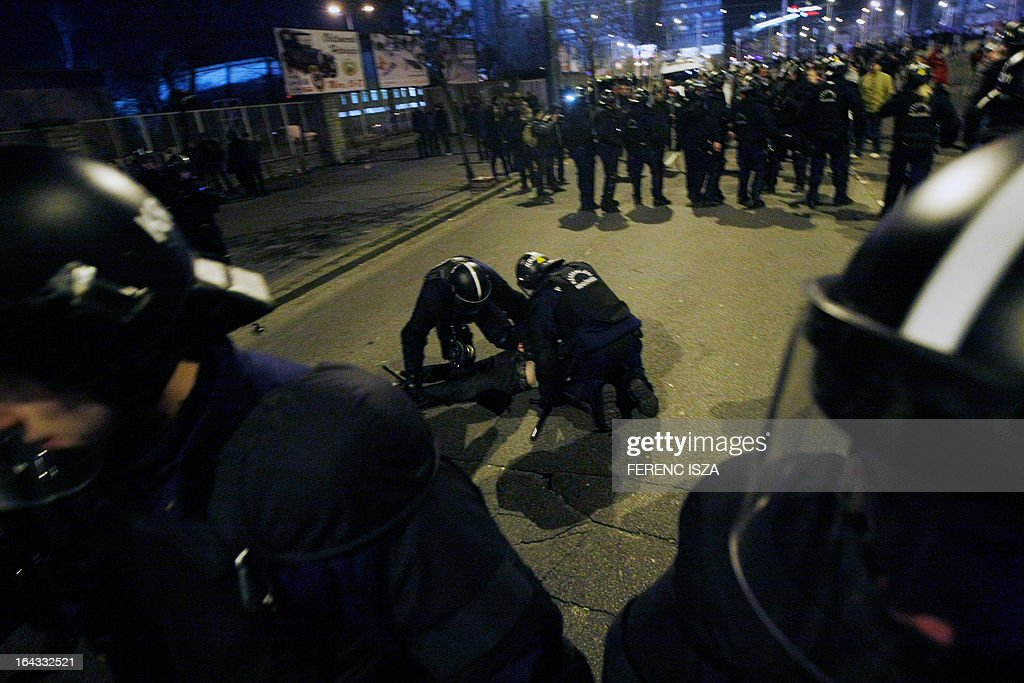 Riot police detain a Hungarian fan outside of the Puskas stadium after the Hungary vs Romania FIFA 2014 World Cup qualifying football match in Budapest, on March 22, 2013. FIFA ordered Hungary to play the 2014 World Cup qualifier match behind closed doors after fans hurled anti-Semitic abuse during a friendly match with Israel in August 2012.