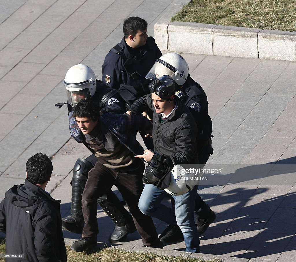 Riot police detain a protester as demonstrators try to march to the parliament building in Ankara during to protest the Turkish prime minister and Turkey's ruling Justice and Development Party (AKP) on February 13, 2014. Turkish riot police on February 13 fired tear gas and water cannon at around 2,000 protesters demanding the release of army officers jailed for plotting a coup. At least 12 protesters were arrested and two people, including a police officer, were injured in clashes.