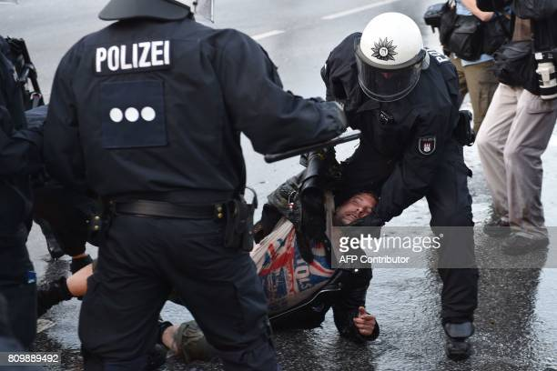 Riot police detain a protester during the 'Welcome to Hell' rally against the G20 summit in Hamburg northern Germany on July 6 2017 Leaders of the...