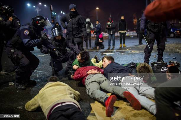 TOPSHOT Riot police detain protesters during a protest in front of the government headquarters against controversial decrees to pardon corrupt...