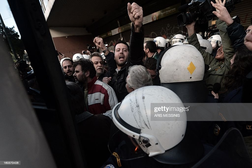 Riot police detain protesters outside the Labour Ministry in Athens on January 30, 2013. Police were called in on Wednesday to dislodge around 30 Communist unionists from the labour ministry in a protest against new pension cut plans. The unionists were arrested and police used tear gas outside the building to disperse a larger group of protesters demanding their release.